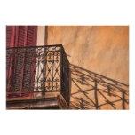 Balcón rojo del hierro del obturador en una casa f fotos