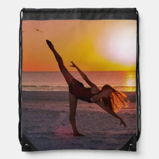 Ballet de la puesta del sol en la playa mochila