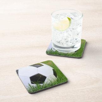 Balón de fútbol clásico en la hierba posavasos de bebida