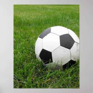 Balón de fútbol en hierba póster