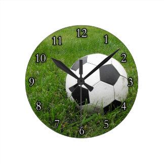 Balón de fútbol en hierba reloj redondo mediano