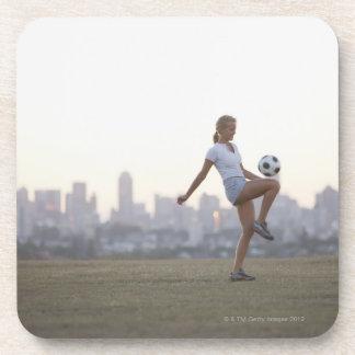 Balón de fútbol kneeing de la mujer en parque posavaso