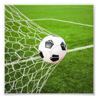 Balón de fútbol que golpea la red de la meta fotografías