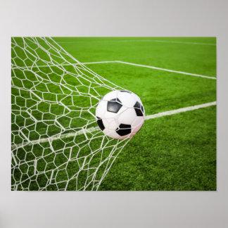 Balón de fútbol que golpea la red de la meta póster