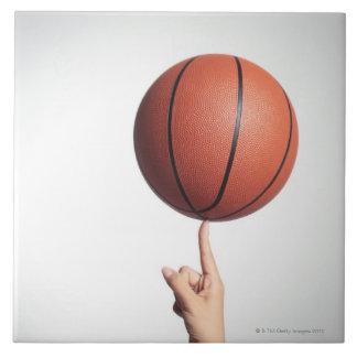Baloncesto en el dedo índice, primer de las manos azulejo cuadrado grande