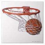 Baloncesto que pasa a través de aro azulejos