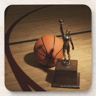 Baloncesto y trofeo en la cancha de básquet, posavasos