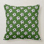 Balones de fútbol blancos y negros en verde almohada