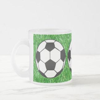 Balones de fútbol en césped taza de café esmerilada