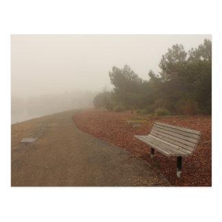 Banco de parque en la postal de la niebla