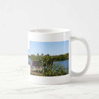 Banco en muelle con el cielo azul de la reserva na tazas de café