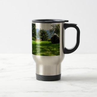 Banco en un prado con la piedra taza de viaje de acero inoxidable