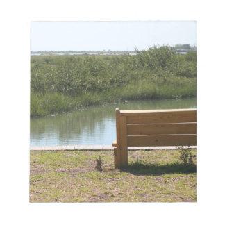 Banco por el río con la hierba y agua libreta para notas