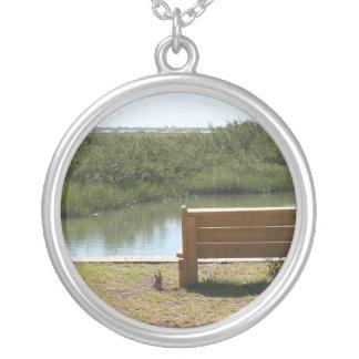 Banco por el río con la hierba y agua colgante redondo