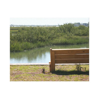 Banco por el río con la hierba y agua impresion de lienzo