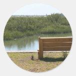 Banco por el río con la hierba y agua pegatinas redondas