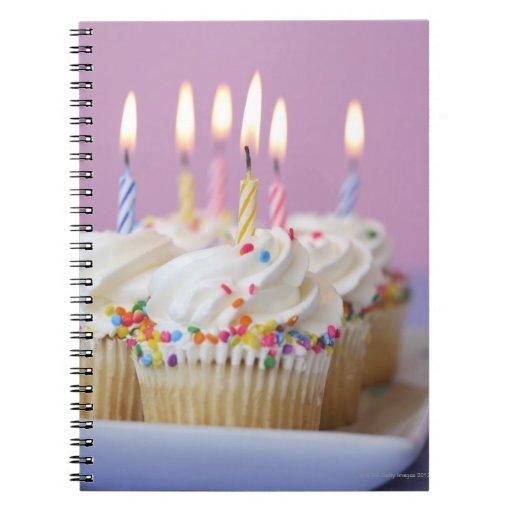 Bandeja de magdalenas del cumpleaños con las velas libreta