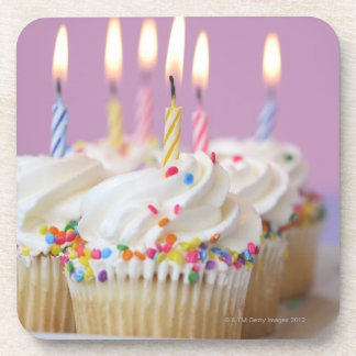 Bandeja de magdalenas del cumpleaños con las velas posavasos de bebidas