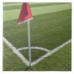 Bandera de la esquina roja en campo de fútbol azulejo cuadrado grande
