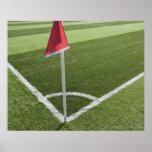 Bandera de la esquina roja en campo de fútbol póster