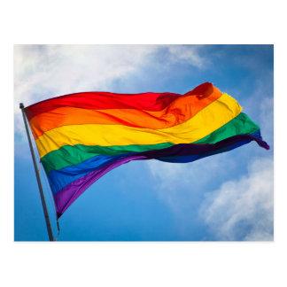 Bandera del arco iris que agita en el viento tarjeta postal