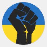 Bandera ucraniana con el puño negro pegatina redonda