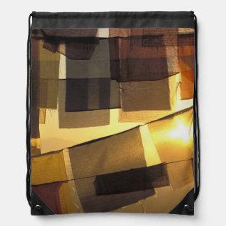 Banderas budistas del rezo en la puesta del sol, mochilas