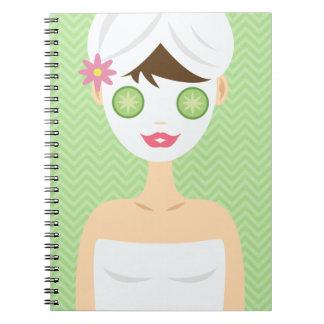 Baño de la mujer con una mascarilla blanca libros de apuntes con espiral