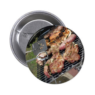 Barbecued steak and sausages on the grill 2 inch round button