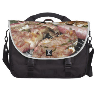 Barbecued steak and sausages on the grill commuter bags