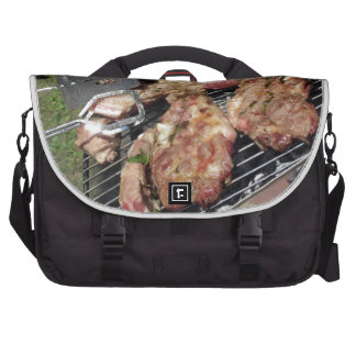Barbecued steak and sausages on the grill laptop bags