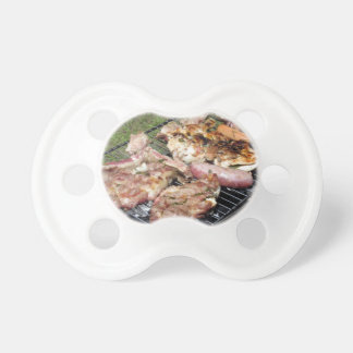 Barbecued steak and sausages on the grill pacifier