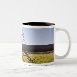 Barbed wire rolled up on fencerow near Two-Tone coffee mug