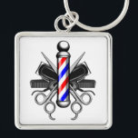 """Barbershop Logo Keychain<br><div class=""""desc"""">Barbershop logo style design with classic red,  white and blue striped barber pole standing proud in center. Barber life tools of the trade in back. Illustrated tools include crossed hair clippers,  crossed barber scissors and black combs.</div>"""
