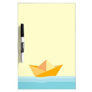 Barco de papel amarillo sobre mar azul pizarra blanca