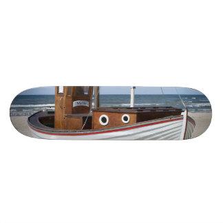 Barco de pesca de madera en la playa tablas de patinar