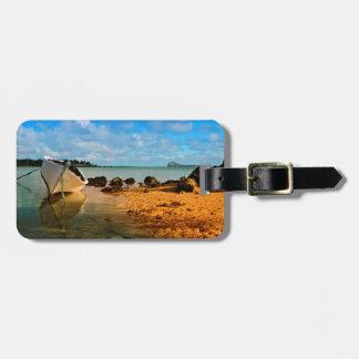 Barco de pesca en la playa mauriciana con el etiquetas de maletas
