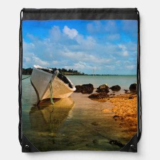 Barco de pesca en la playa mauriciana con el mochilas