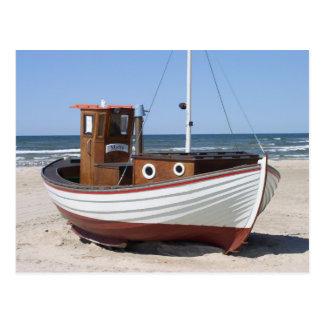 Barco de pesca náutico que se sienta en la playa d postales