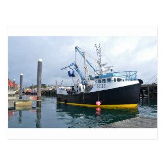 Barco de pesca que sale del puerto postales