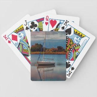Barco de vela vacío en el lago, naipe barajas de cartas