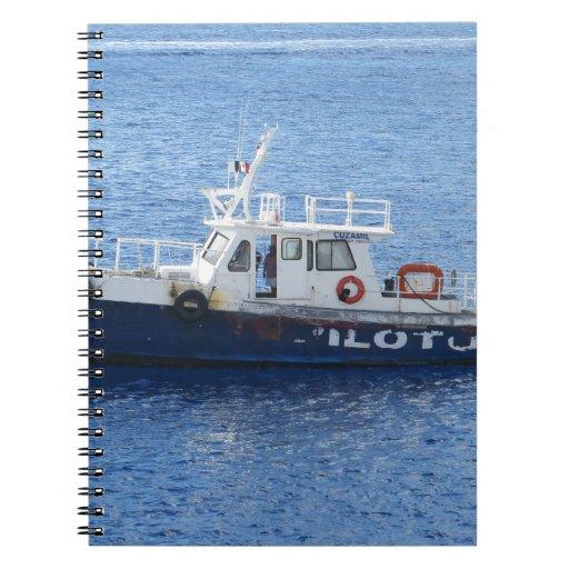 Barco del tirón en el agua azul cuaderno