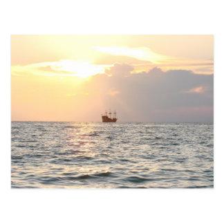 Barco pirata en puesta del sol tarjeta postal