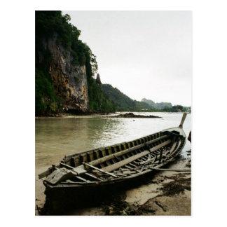 Barco quebrado a lo largo del cauce del río tarjetas postales