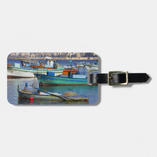 Barcos de pesca coloridos en el puerto de etiquetas maletas