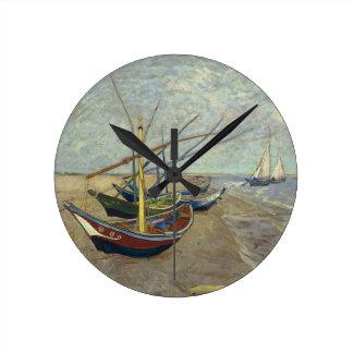 Barcos de pesca en el reloj de pared de la playa