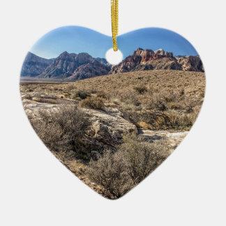 Barranco rojo de la roca y cauce del río seco adorno navideño de cerámica en forma de corazón