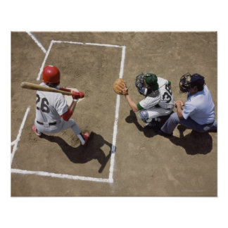 Baseball batter awaiting pitch with catcher and poster