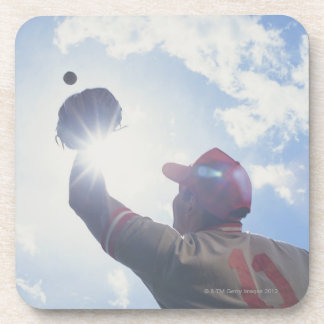 Baseball player catching ball with sun in his coaster