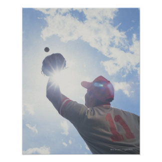 Baseball player catching ball with sun in his print